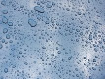 Drops on car. Drops on blue car mirror sky royalty free stock photography