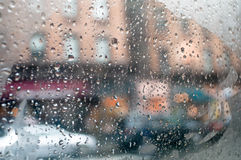 Drops on a car window. Countless rain drops filter the view from inside a car Royalty Free Stock Image