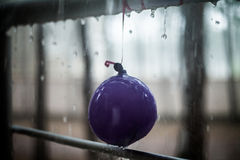 Drops on the child balloon and metal handrail, summer rain stock photo