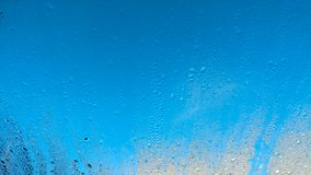 Water drops on windows with light blue sky Royalty Free Stock Images