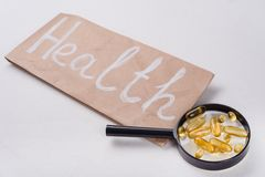 Drops for fish oil with omega 3 and vitamin D on the magnifier, the concept of healthy eating. Close-up Stock Photo