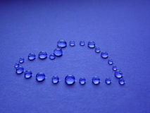 Drops in the form of heart on a blue background. Contour heart of drops on a blue background Stock Photography