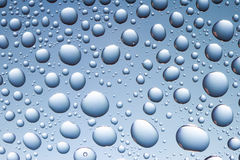 Drops on the glass. Many blue water drops on the glass Stock Photography