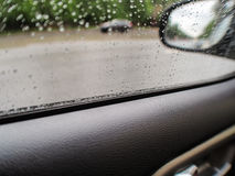 Drops on glass. Raindrops on the glass of the car, the driver`s door Stock Image
