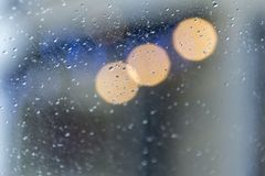 Drops on glass and the shining city fires - a soft background stock images