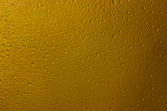 Drops on glass of yellow color from a rain Royalty Free Stock Photo