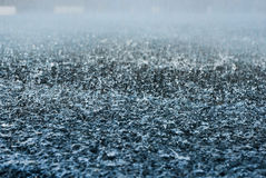 Drops of heavy rain on asphalt road. In the city Royalty Free Stock Photography