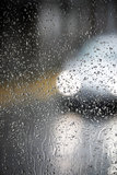 Drops and lights. An out of focus lights of a car and a glass with many rain drops Royalty Free Stock Images
