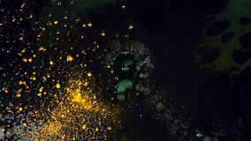 Drops of liquid soap falling in black substance with yellow dry inks floating on the surface. Colorful reaction on. Mixing inks and soap stock footage