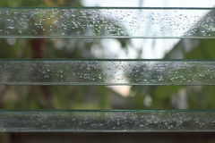 Drops on louver glass after rain. Stock Photos