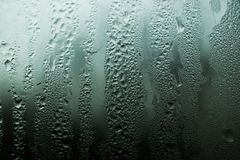 Drops of moisture on misted glass. Drops of moisture flowing down the misty glass Stock Images