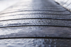 Drops of morning dew on a wooden bench in the park Stock Photo