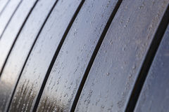 Drops of morning dew on a wooden bench in the park Stock Photos