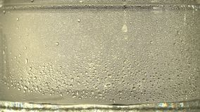 Drops of pure water or alcohol drip inside a glass jar, on silver background. The distillation process. Close-up. Drops of pure water or alcohol drip inside a stock video footage