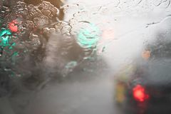 Drops Of Rain Drizzle on the glass windshield in the evening. street in the heavy rain. Bokeh Tail light. soft Focus. Please drive carefully, slippery road stock photo