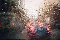 Drops Of Rain Drizzle on the glass windshield in the evening. street. In the heavy rain. Bokeh Tail light. soft Focus. Please drive carefully, slippery road royalty free stock photo