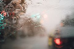 Drops Of Rain Drizzle on the glass windshield in the evening. street in the heavy rain. Bokeh Tail light. soft Focus. Please drive carefully, slippery road royalty free stock photos