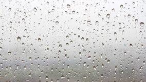 Drops of rain flow down the window glass