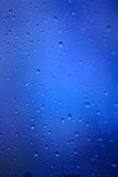 Drops of rain on a glass on a blue background Royalty Free Stock Images