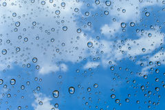 Drops of rain on glass and blue sky background / drops on glass Royalty Free Stock Images