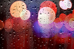 Drops of rain on glass with defocused lights. Abstract backgroun Stock Photos
