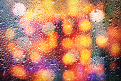 Drops of rain on glass with defocused lights. Abstract blurred b Stock Image