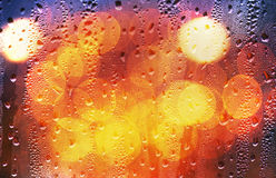 Drops of rain on glass with defocused lights Royalty Free Stock Images