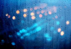 Drops of rain on glass with defocused lights. Urban abstract bac Stock Photos