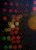 Drops of rain on glass with defocused lights. Urban abstract bac Stock Photography
