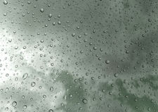 Drops of rain on glass , rain drops on clear window / rain drops with clouds / water drops on glass after rain background / water. Drops Stock Images