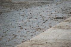 Drops of rain shower on the gray asphalt near the water drain grid Stock Photo