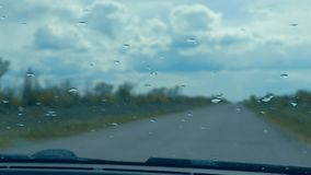 Drops of rain water on the windshield of the car traffic road autumn stock video footage