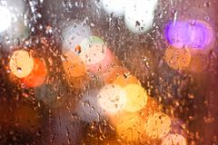 Drops of rain on a window, on a background of a bokeh from the lights of a night city. Drops of rain on a window, on  background of a bokeh from the lights of a Royalty Free Stock Photo