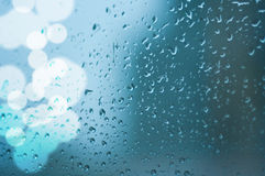 Drops of rain on window glass. Natural drops of rain on window glass with lights bokeh stock photography