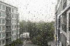 Drops of rain on a window pane. Drops of rain on a window pane, buildings in background royalty free stock photography