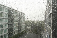 Drops of rain on a window pane. Drops of rain on a window pane, buildings in background royalty free stock photos