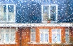 Drops of Rain on Window Pane. Drop of rain on window pane, blurry terrance house in background stock photography