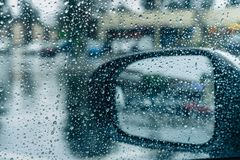Drops of rain on the window and on the wing mirror. Wet pavement in the background royalty free stock photography