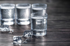 Drops on shot with vodka. Close-up shot of few transparent shots with vodka and ice cubes near Royalty Free Stock Photography