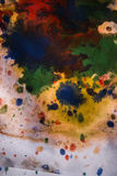 Drops with streaks of different colors paint are mixed and absorbed Royalty Free Stock Photos