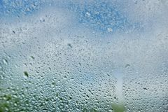 Drops of summer rain on the window glass of fresh blue and white. Clouds background texture royalty free stock photography