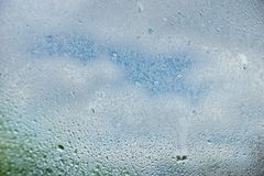 Drops of summer rain on the window glass of fresh blue and white. Clouds background texture royalty free stock images