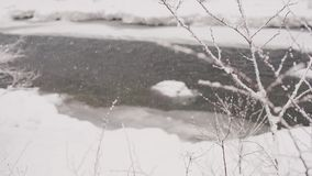 Drops thick snow against the background of a mountain river. Slow motion stock footage