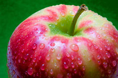 Drops of water on an apple closeup on green textured background Stock Photography