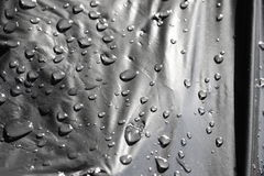 Drops of water on black plastic Stock Photography