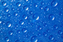 Drops of water on blue background Stock Photos