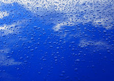 Drops of water on the blue car bonnet Royalty Free Stock Images