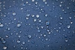 Drops of water. On blue waterproof cloth, Close-up royalty free stock image