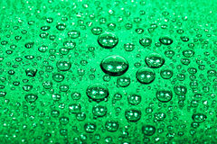 Drops of water on a color background. Green. Shallow depth of fi Stock Images