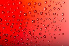 Drops of water on a color background. Red tone Royalty Free Stock Image